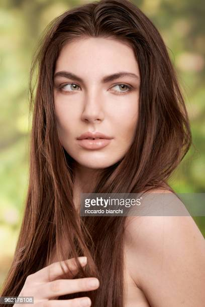 BRUNETTE WOMAN WITH NATURAL LOOK AND GREEN EYES ON NATURE BACKGROUND