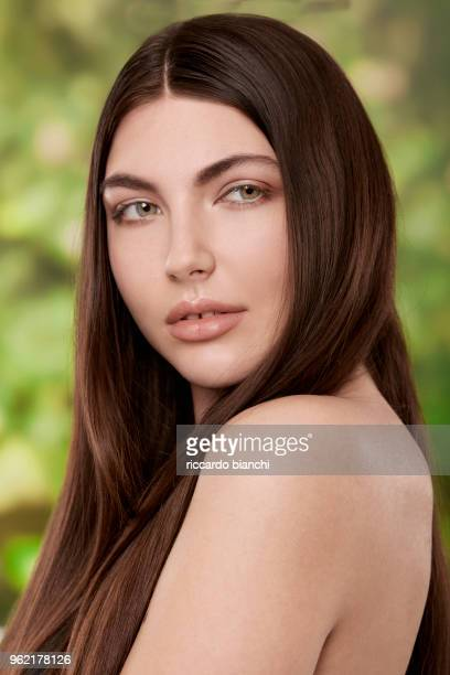 BRUNETTE WOMAN WITH NATURAL LOOK AND STRAIGHT HAIR ON NATURE BACKGROU