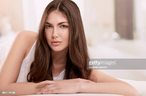 brunette woman with long hair laying on her bed - ストレートヘア ストックフォトと画像