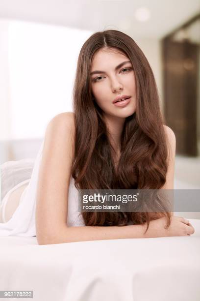 BRUNETTE WOMAN WITH LONG HAIR LAYING ON HER BED