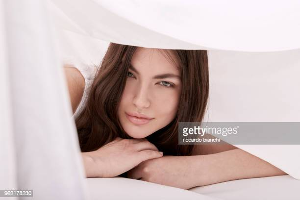 BRUNETTE WOMAN WITH LONG HAIR LAYING UNDER BED SHEETS
