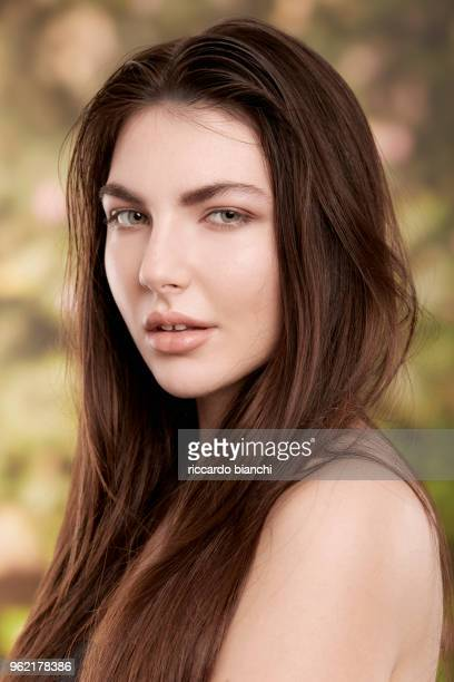 BRUNETTE WOMAN WITH NATURAL LOOK ON NATURE BACKGROUND