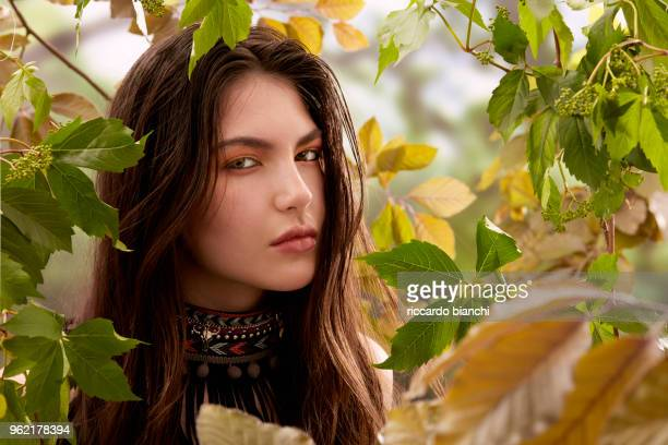BRUNETTE WOMAN LOOKING THROUGH TREES