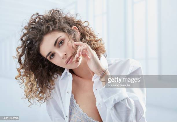 natural look woman with curly hair wearing a white shirt - wavy hair stock pictures, royalty-free photos & images