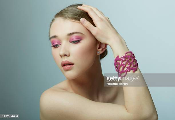 BLONDE WOMAN WITH PINK EYESHADOW AND TIED HAIR