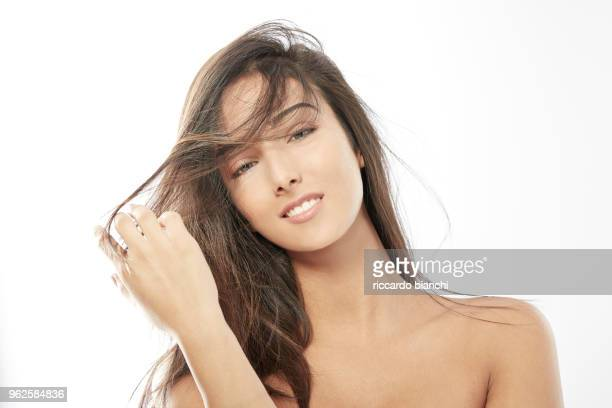 NATURAL LOOK BRUNETTE WOMAN HOLDING HER STRAIGHT HAIR
