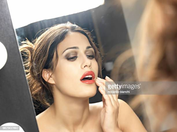 brunette woman with lipstick looking in the mirror - ator imagens e fotografias de stock