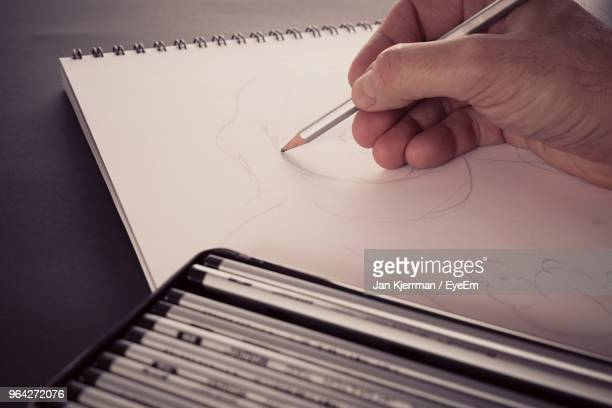 cropped hand of man drawing in paper at table - pencil drawing stock pictures, royalty-free photos & images
