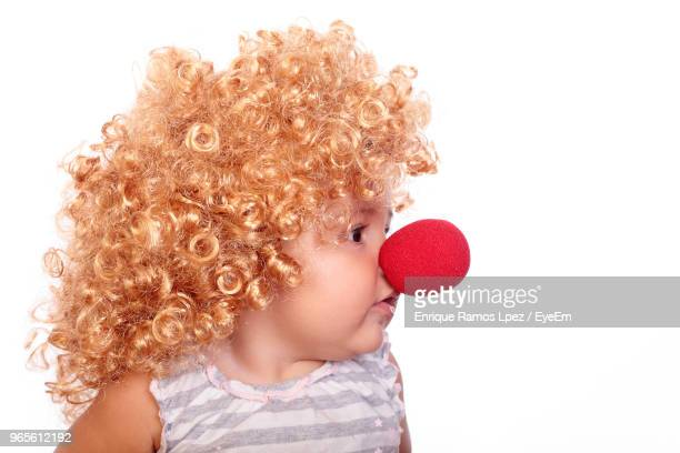 close-up of cute girl wearing wig and clowns nose against white background - clown's nose stock photos and pictures