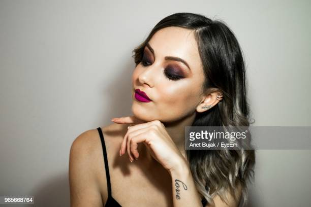 Close-Up Of Beautiful Young Woman Wearing Make-Up Against Wall