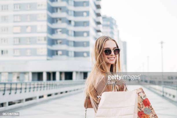 portrait of a smiling woman carrying shopping bags - merchandise stock pictures, royalty-free photos & images