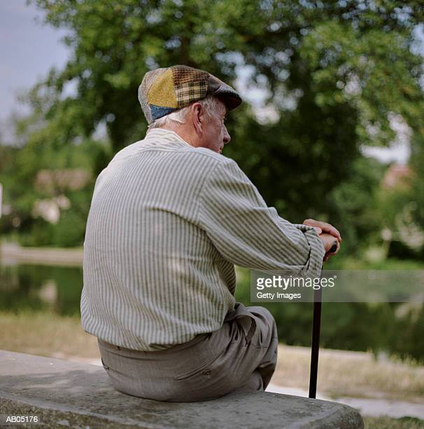 back view of elderly man, sitting on stone bench - flat cap stock pictures, royalty-free photos & images