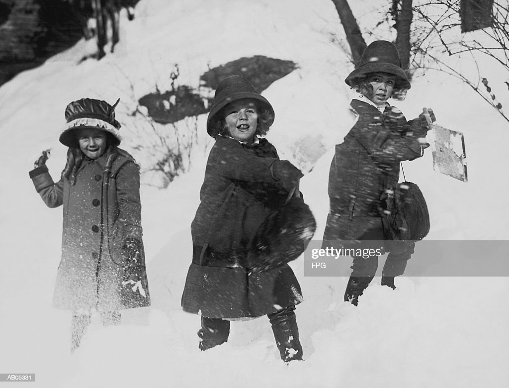 THREE GIRLS IN WINTER COATS, PLAYING IN THE SNOW : Stock Photo