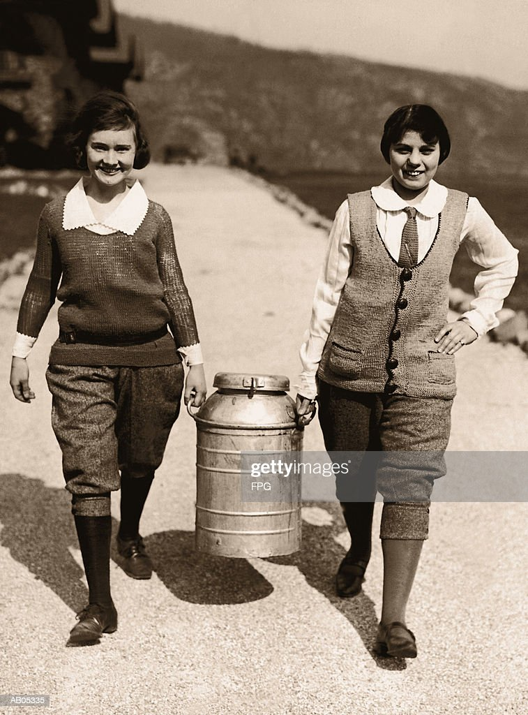 TWO TEENAGE GIRLS CARRYING A MILK CHURN / ARCHIVE SHOT : Stock Photo