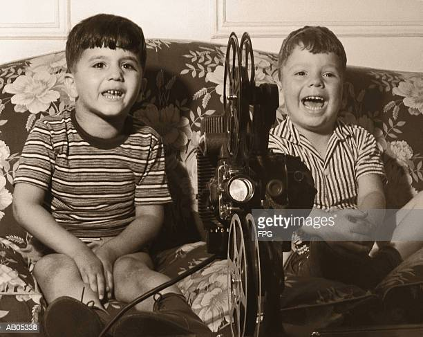TWO BOYS WATCHING A HOME MOVIE USING AN OLD PROJECTOR / 1960'S