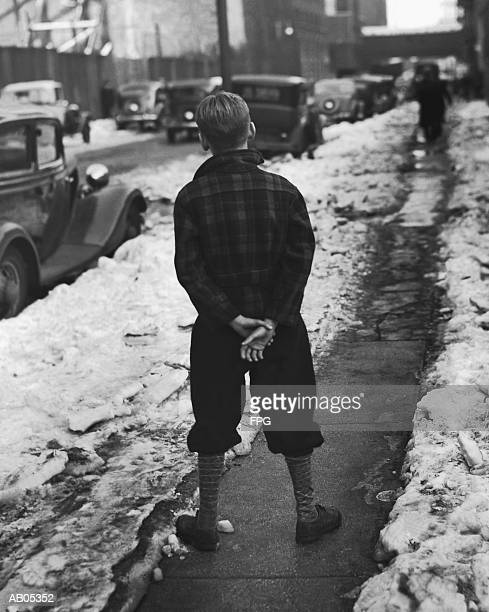 boy standing on sidewalk - knickers stock-fotos und bilder