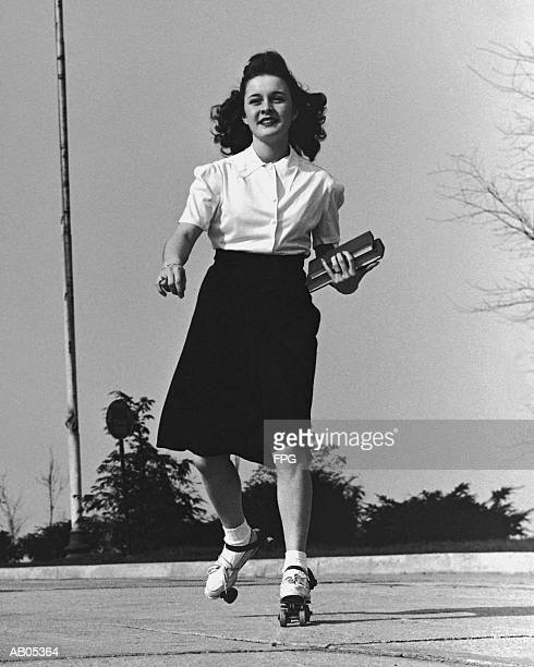 TEENAGE GIRL ROLLER SKATING TO COLLEGE, CARRYING BOOKS / 1950'S