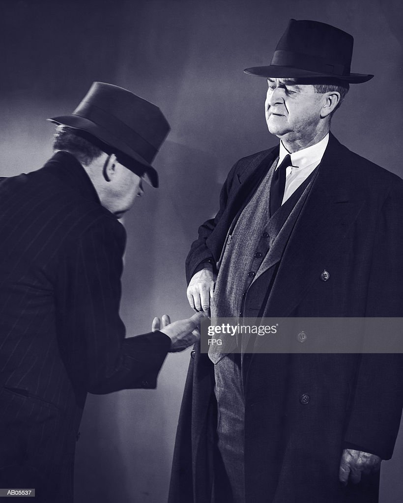 BUSINESSMAN DONATING MONEY TO A POOR MAN BEGGING : Stockfoto