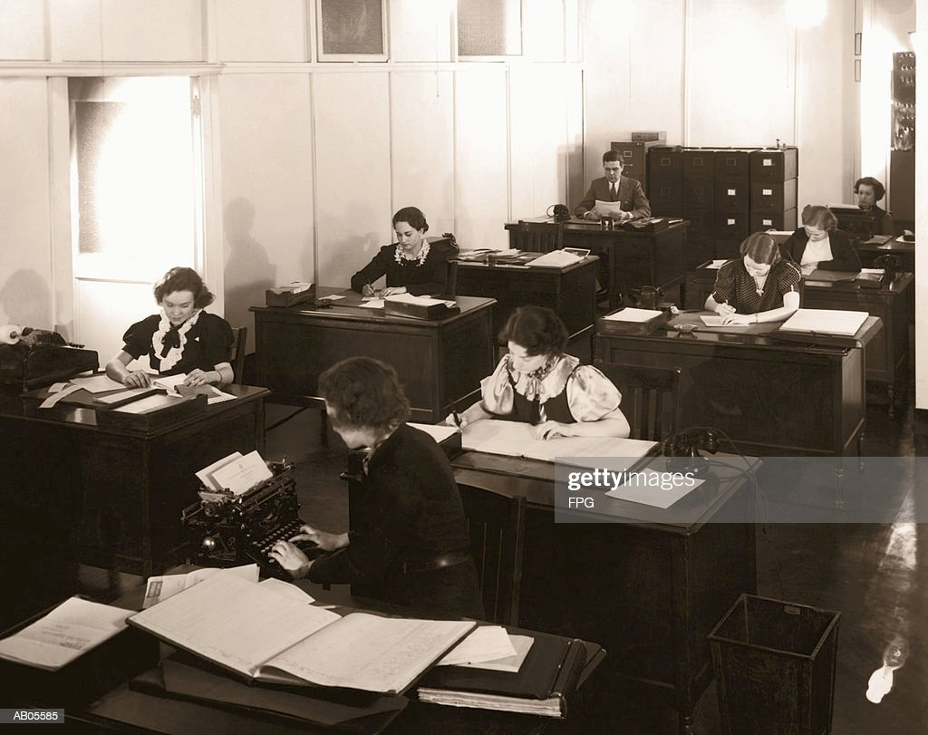 ARCHIVE SHOT / GROUP OF OFFICE WORKERS SITTING AT THEIR DESKS : Stock Photo