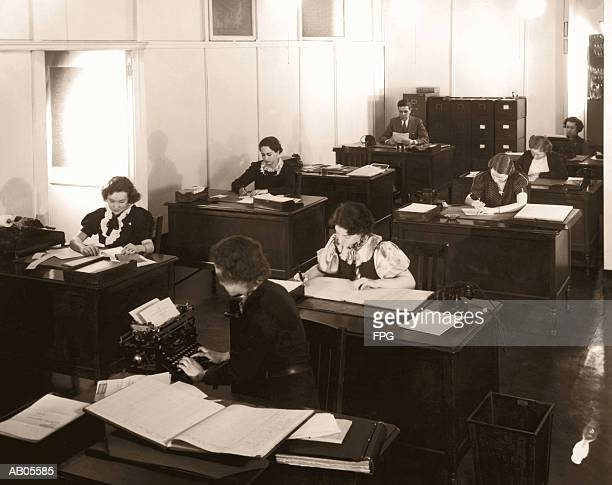 archive shot / group of office workers sitting at their desks - 1957 stockfoto's en -beelden