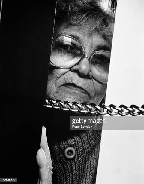 elderly woman at door with security chain on b/w - door lock stock pictures, royalty-free photos & images