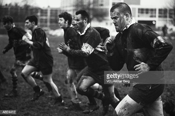 GROUP OF RUGBY PLAYERS RUNNING ON PITCH DURING TRAINING SESSION