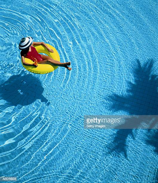 WOMAN FLOATING IN POOL ON RING