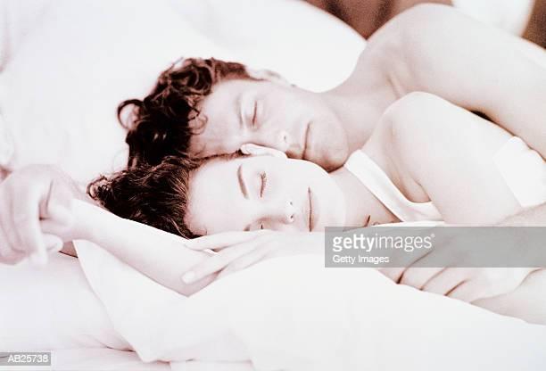 couple sleeping - abbracciarsi a letto foto e immagini stock