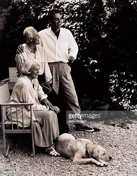 parents with son and dog in garden - un animal fotografías e imágenes de stock