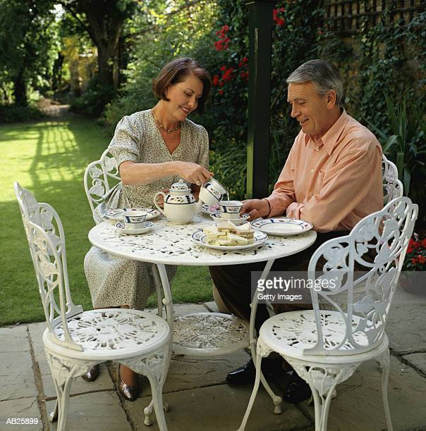 MIDDLE AGED COUPLE HAVING AFTERNOON TEA ON PATIO