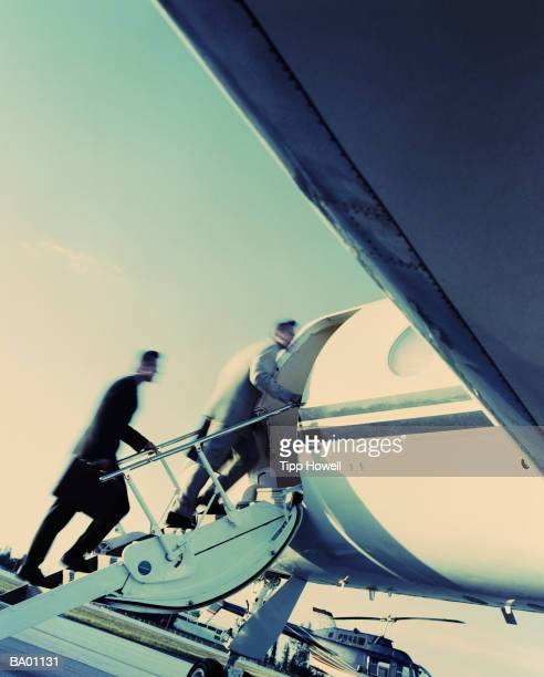 TWO BUSINESSMEN ASCENDING STEPS INTO AIRCRAFT ON RUNWAY