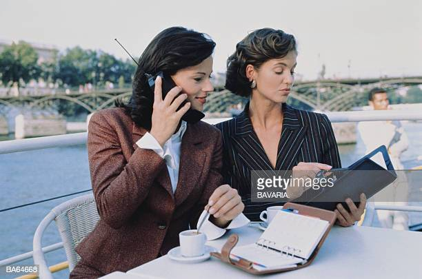 TWO BUSINESSWOMEN SITTING AT CAFE BY WATERFRONT, PARIS,FRANCE