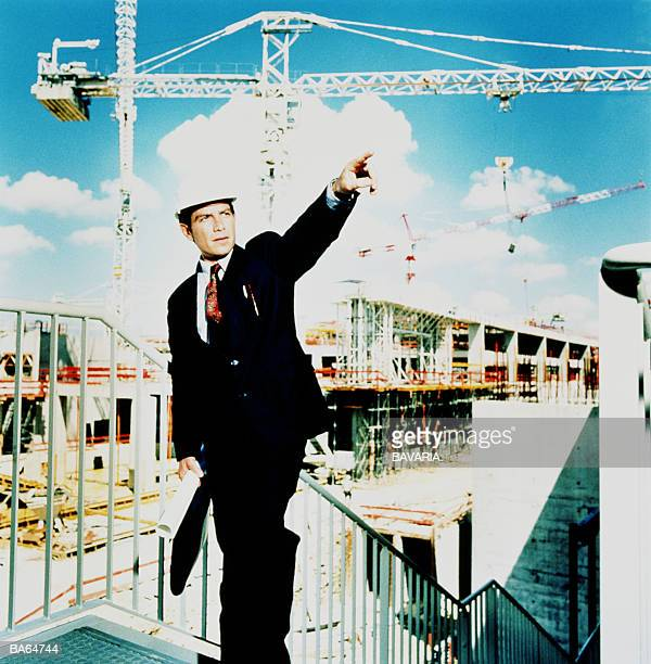 ARCHITECT WEARING HARD HAT ON CONSTRUCTION SITE