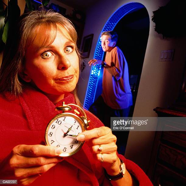 teen boy getting home late upset mum waiting with clock - curfew stock pictures, royalty-free photos & images