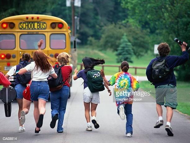 eighth grade students running to catch school bus - écolière photos et images de collection