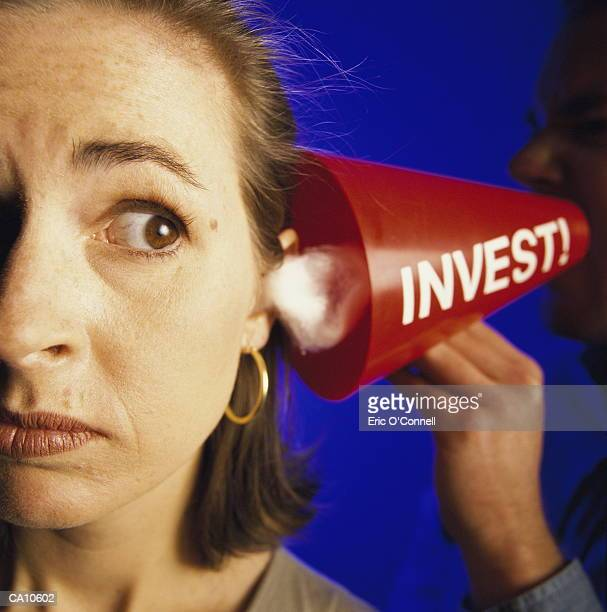 WOMAN WITH INVESTMENT MEGAPHONE AT HER EAR