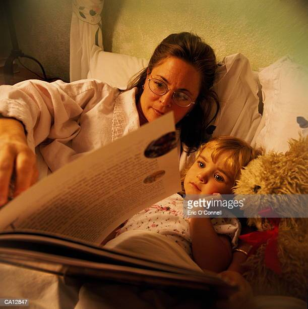 MOM READING TO DAUGHTER IN BED