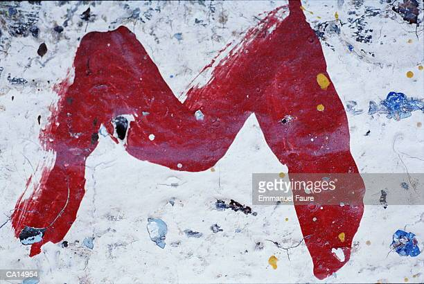 CLOSE-UP / RED LETTER 'M' PAINTED ON BRICK WALL