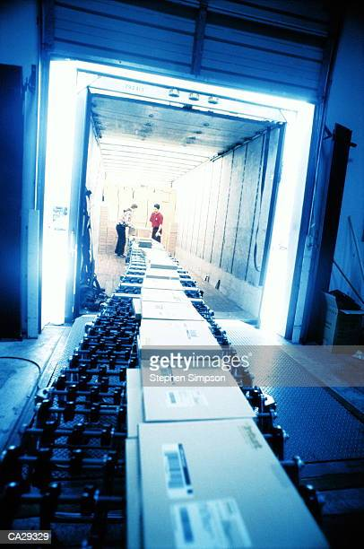 WORKERS LOADING TRUCK WITH BOXES FROM CONVEYOR BELT