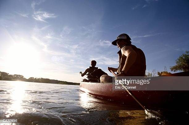 couple canoeing on lake - canoeing stock pictures, royalty-free photos & images