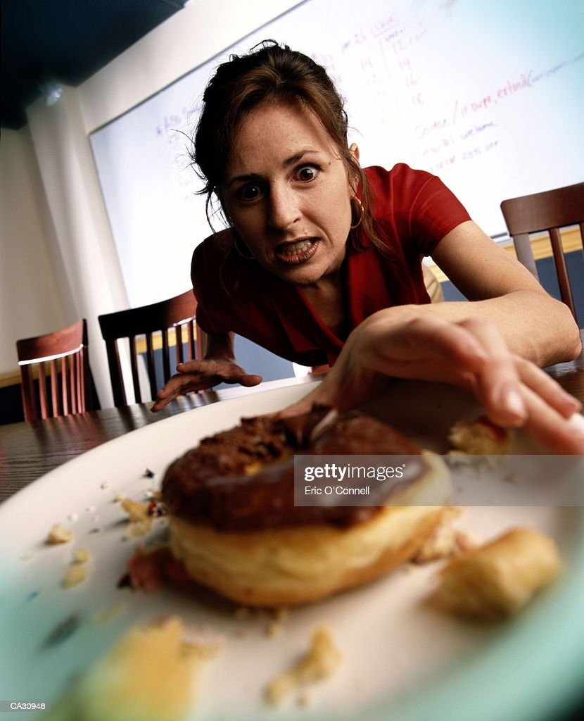 WOMAN REACHING FOR BURGER ONTABLE : Stock-Foto