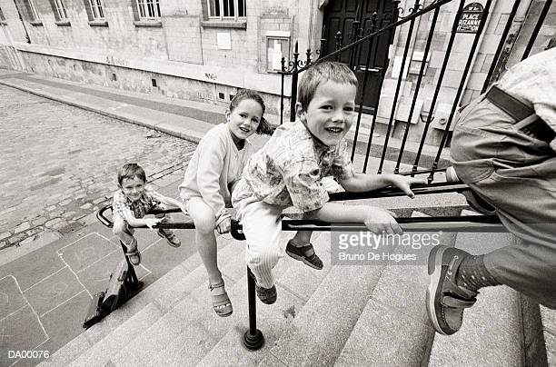 four children sitting on hand rail above flight of steps - railing stock photos and pictures