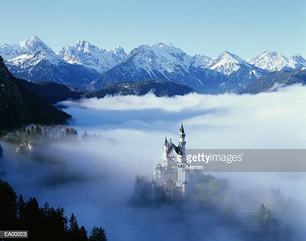 NEUSCHWANSTEIN CASTLE IN MIST, WITH MOUNTAINS BEHIND / BAVARIA BAVARIA