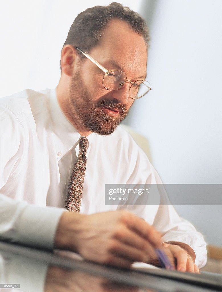AN EXECUTIVE IN A WHITE SHIRT AND TIE HOLDS A PEN AS HE WORKS : Stockfoto