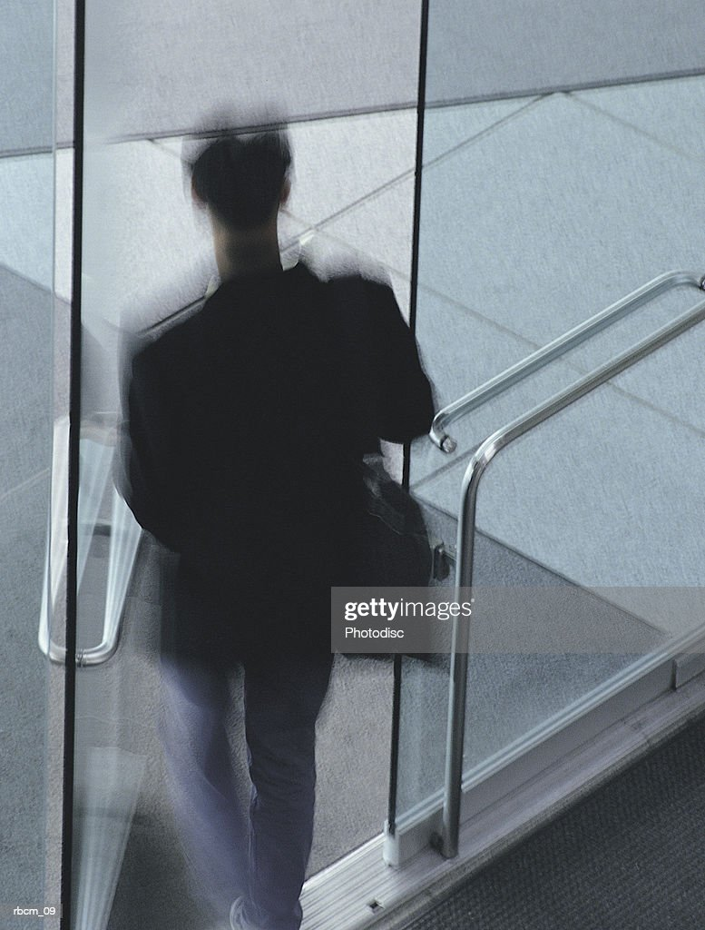 A Blurred Man In Jeans And A Blazer Exits A Building To The Street