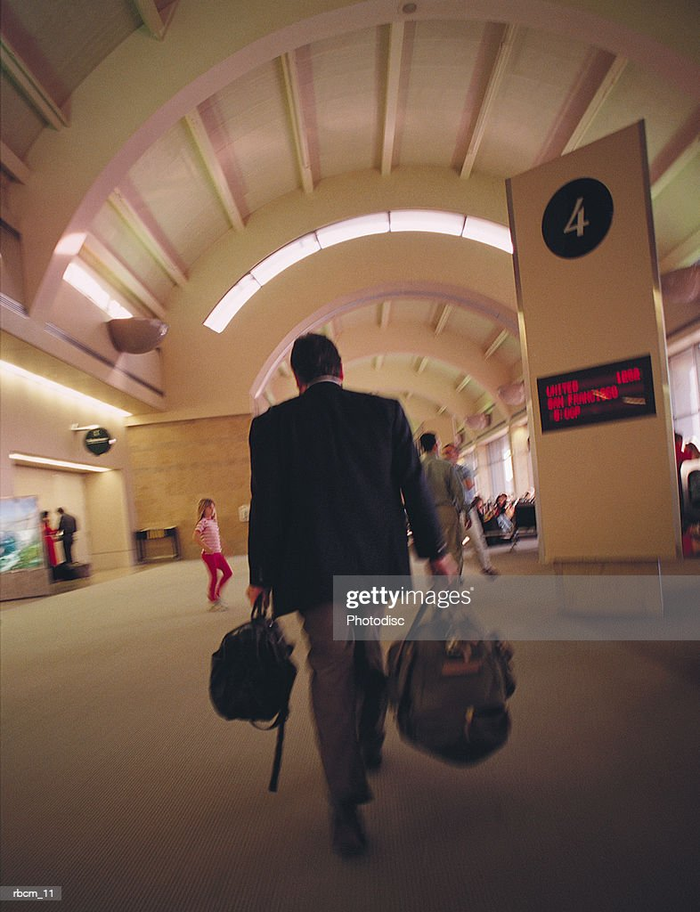 A BUSINESSMAN DRESSED IN A SUIT WALKS THROUGH AN AIRPORT AS HE CARRIES HIS BAGGAGE : Stockfoto