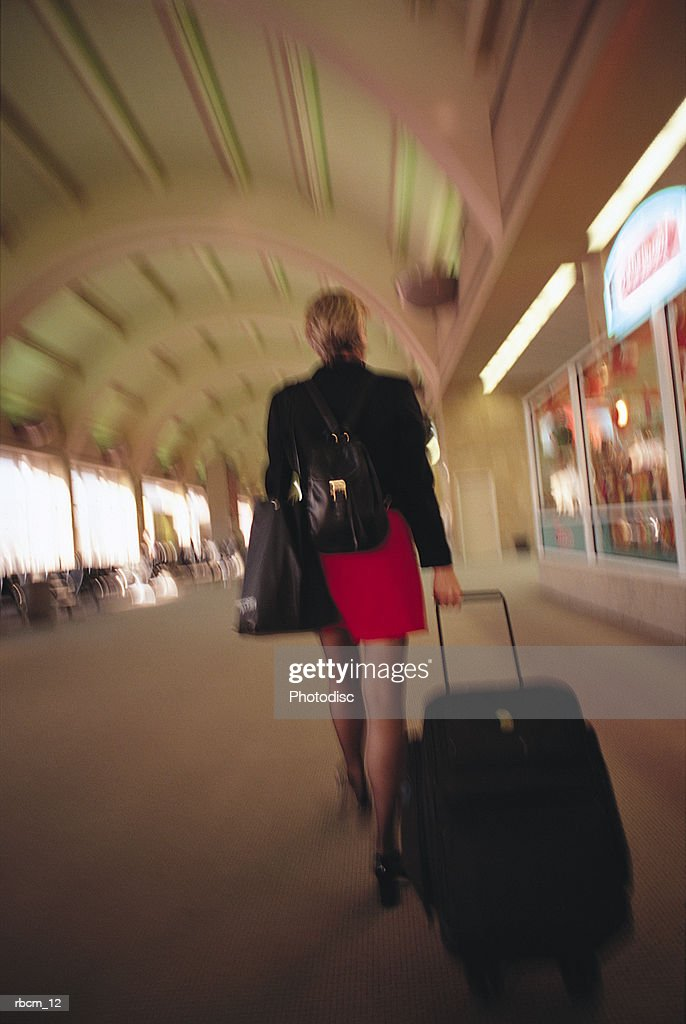 A BUSINESSWOMAN DRESSED IN A RED SKIRT AND A BLACK BLAZER WALKS THROUGH AN EMPTY AIRPORT WHILE CARRYING HER LUGGAGE : Stockfoto