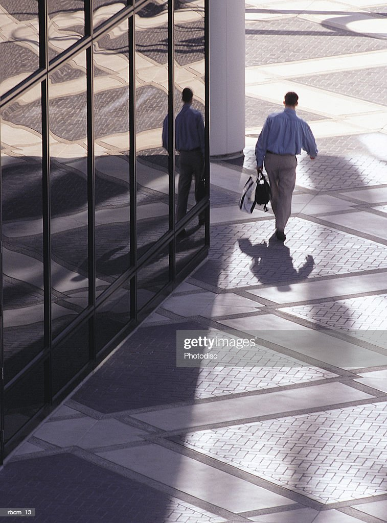 A BUSINESS MAN WALKS ALONG A GLASS BUILDING WHILE CARRYING A BRIEF CASE : Stockfoto
