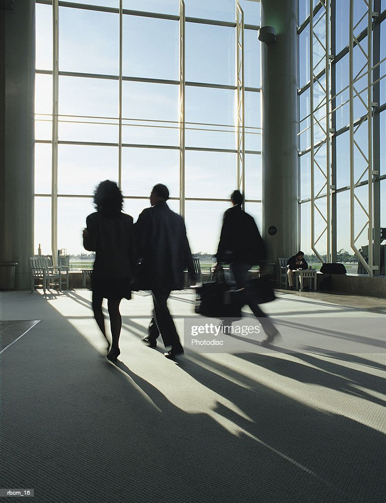 THREE WOMEN WALK THROUGH AN EMPTY AIRPORT WHILE THE SUN SHINES THROUGH LARGE GLASS WINDOWS. : Stockfoto