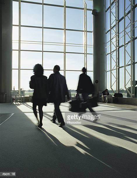 three women walk through an empty airport while the sun shines through large glass windows. - 職業 ポーター ストックフォトと画像